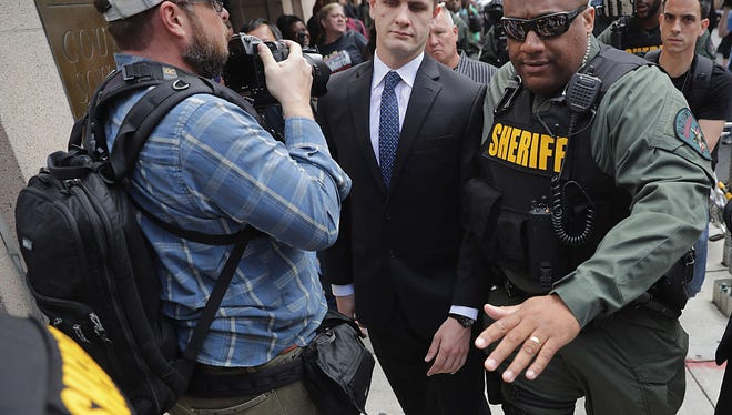 Baltimore City Sheriff's Deputies clear a path for Baltimore Police Officer Edward Nero's family members as demonstrators and members of the news media crowd around outside the Mitchell Courthouse-West after Nero was found not guilty on all charges against him related to the arrest and death of Freddie Gray May 23, 2016 in Baltimore, Maryland. One of six police officers charged, Nero was found not guilty by Baltimore Circuit Judge Barry Williams in a bench trial.
