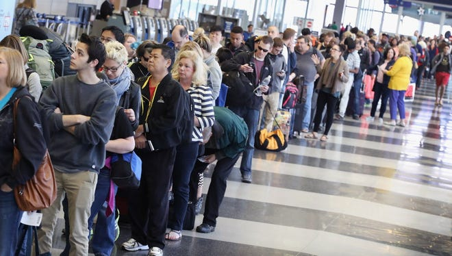 Passengers at Chicago O'Hare International Airport wait in line to be screened at a Transportation Security Administration checkpoint on May 16, 2016 in Chicago, Illinois.