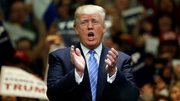 Republican presidential candidate Donald Trump applauds