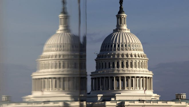 This Jan. 8, 2013, file photo shows the Capitol reflected in the windows of the Newseum, on Pennsylvania Avenue in Washington.