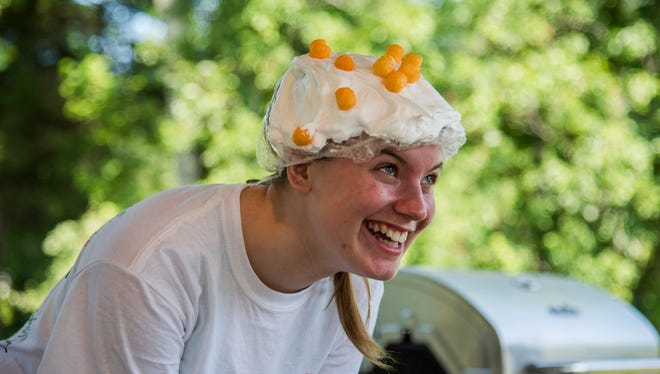 Volunteers and campers at Camp Quality play a game where the player has to land as many cheese puffs on someone's pie-covered head as possible.