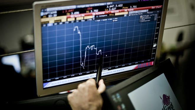 A trader point at a graphic on a computer screen in Lisbon on April 23, 2014 during the auction of Portuguese Treasury Bills.