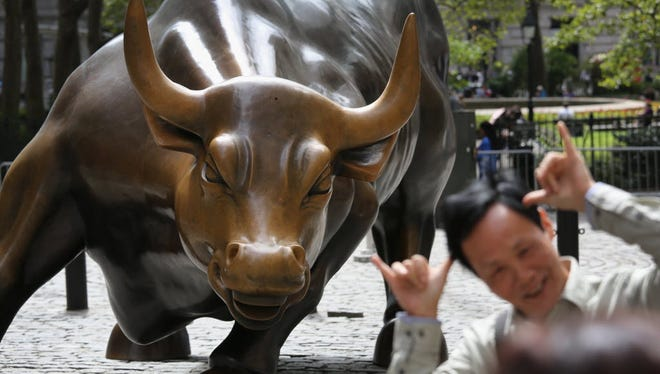 Tourists pose in front of the iconic bull near Wall Street.