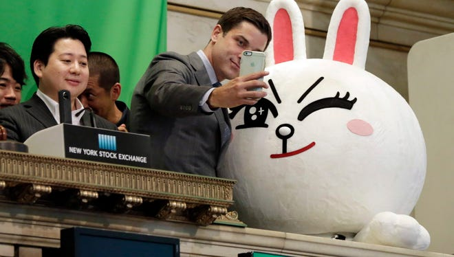 New York Stock Exchange President Tom Farley, center, takes a selfie with Line character Cony on the bell podium on July 14, 2016.