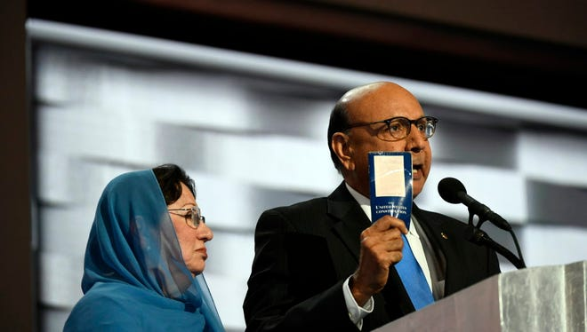 Khizr Khan, father of fallen U.S. soldier Humayun S.M. Khan, offers a copy of the Constitution to Donald Trump as he speaks during the 2016 Democratic National Convention at Wells Fargo Center.