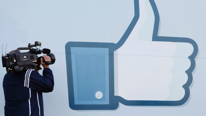 This file photo taken on May 18, 2012 shows a videographer shooting the side of Facebook's Like Button logo displayed at the entrance of the Facebook Headquarters in Menlo Park, California.