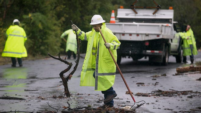 Floyd Taylor, with the City of Austin Watershed Protection department, cleans debris from the road Oct. 24, 2015, in Austin, Texas, after a powerful storm.