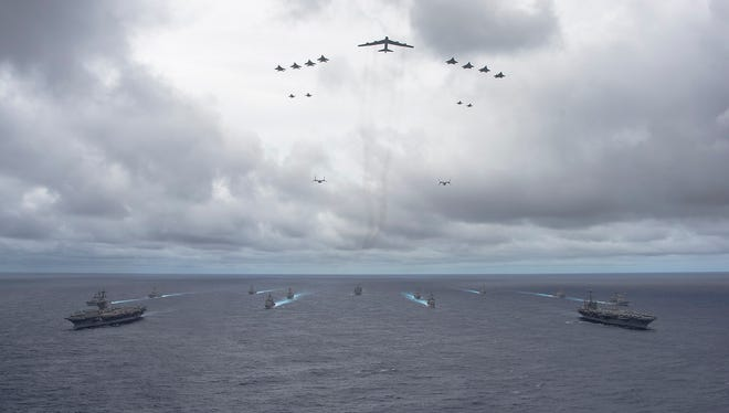 PACIFIC OCEAN (Sept. 23, 2014) Ships from the George Washington and Carl Vinson Carrier Strike Groups and aircraft from the Air Force and Marine Corps operate in formation at the conclusion of Valiant Shield 2014. Valiant Shield is a U.S.-only exercise integrating Navy, Air Force, Army, and Marine Corps assets, offering real-world joint operational experience to develop capabilities that provide a full range of options to defend U.S. interests and those of its allies and partners. (U.S. Navy photo by Mass Communication Specialist 1st Class Trevor Welsh)