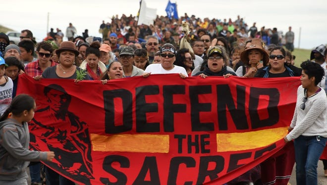 American Indians march to a sacred burial ground disturbed by bulldozers building the Dakota Access Pipeline near the encampment where hundreds of people have gathered to join the Standing Rock Sioux tribe's protest of the oil pipeline that is slated to cross the Missouri River nearby.