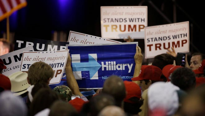 A woman holds up a sign for Democratic presidential candidate Hillary Clinton during a rally for Republican presidential candidate Donald Trump, Thursday, June 2, 2016, in San Jose, Calif.