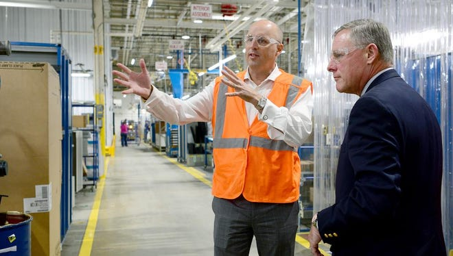 U.S. Sen. Richard Burr, right, talks with general manager Chris Champlin as he tours the ThermoFisher Scientific plant in Weaverville Wednesday.