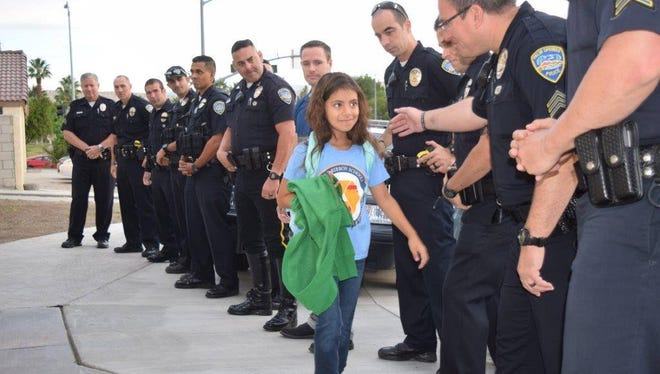 Palm Springs police officers greet Vanessa Vega, the youngest daughter of fallen officer Jose Gilbert Vega, before taking her to school.