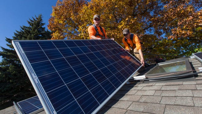 Arch Electric employees and brothers, Kris and Tyler Russell, work on installing solar electric panels on Nov. 4, 2016, at a house in Shorewood, Wis.   MARK  HOFFMAN/MHOFFMAN@JOURNALSENTINEL.COM
