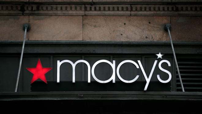 The Macy's sign hangs over its flagship store in Herald Square, August 11, 2016 in New York City.