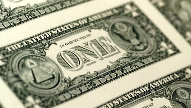 Dollar bills, with backs already printed, go into the press to have face sides printed on at the Bureau of Printing and Engraving.