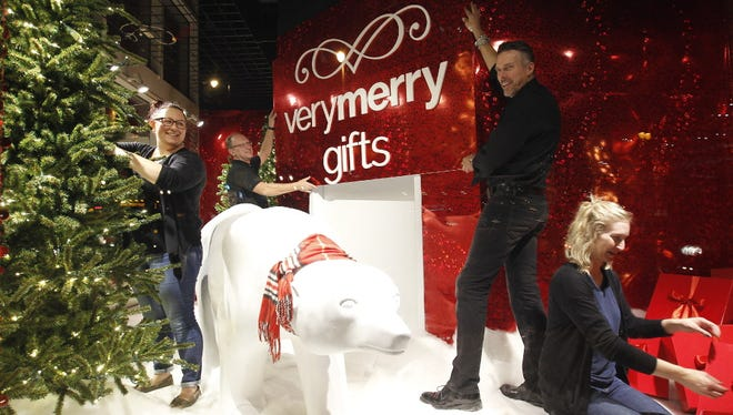 A visual merchandising team for Boston Store prepares a display window for the store at N. 4th St. and W. Wisconsin Ave. for the holiday shopping season.