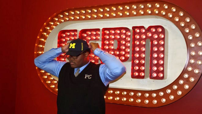 Former Paramus Catholic star Rashan Gary tries on Michigan hat at ESPN studios in Bristol, Conn. Fewer younger people watching TV sports is bad news for ESPN.