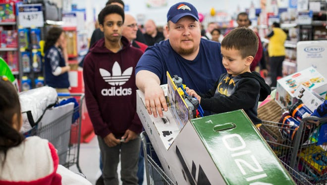 Chris Jolly and his son, Chris Jr., shopping for Black Friday deals in Bentonville, Ark.