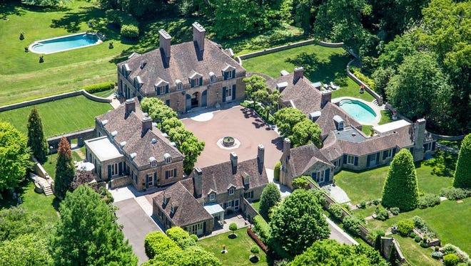 The palatial estate is nestled on 50 private open and wooded acres and consists of the French Normandy-style mansion 14,467 square feet.
