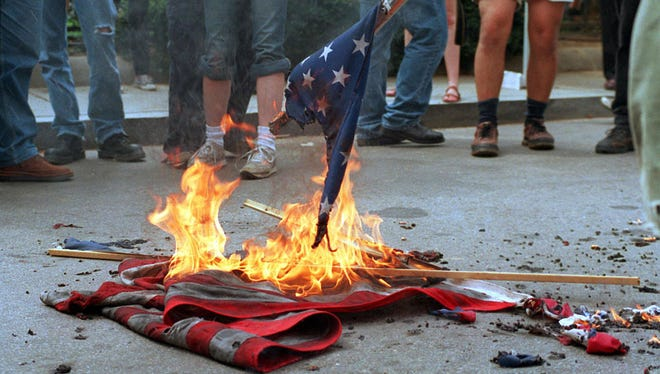 Washington, UNITED STATES:  (FILES): This 20 April 2002 file photo shows demonstrators burning US flags in front of the World Bank headquarters during a protest against the International Monetary Fund - World Bank spring meetings in Washington, DC.  The US Senate began debate 26 June 2006 on a constitutional amendment banning destruction and desecration of the US flag, a symbol so dear to Americans that many display it on their homes or on tiny lapel pins.  The measure is being pushed in response to a 1989 ruling by the US Supreme Court that said flag burning was a form of expression protected by the constitution.  Flag burning was often used by demonstrators protesting the Vietnam War in the 1960s and 1970s. Seventeen years later, the decision remains highly controversial.  AFP PHOTO/FILES/HIROKO MASUIKE  (Photo credit should read HIROKO MASUIKE/AFP/Getty Images)