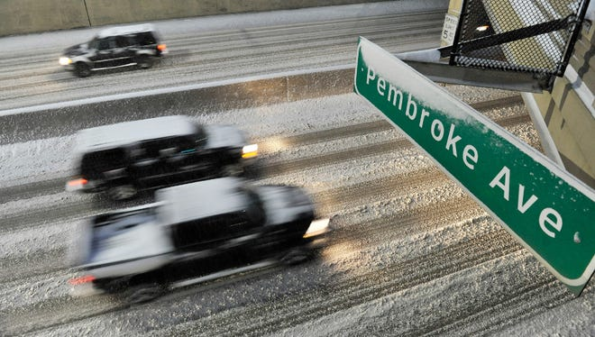 Traffic goes by on the snow-covered Lodge Freeway in Detroit, Sunday, Dec. 11, 2016. Much of Michigan's southern Lower Peninsula, from Lake Michigan to Lake Huron, is under a winter storm warning.