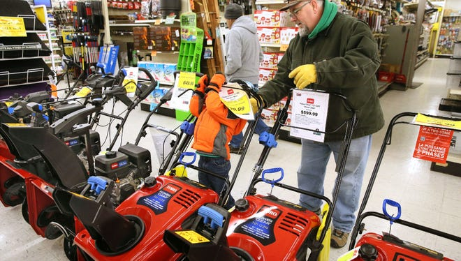 People were shopping for last minute snowstorm supplies at Elliott's Ace Hardware in West Allis on Thursday. Corey Webster of Milwaukee (right) was looking at snowblowers, while his son Kieran Webster age 4 tried to figure out the controls on his own.