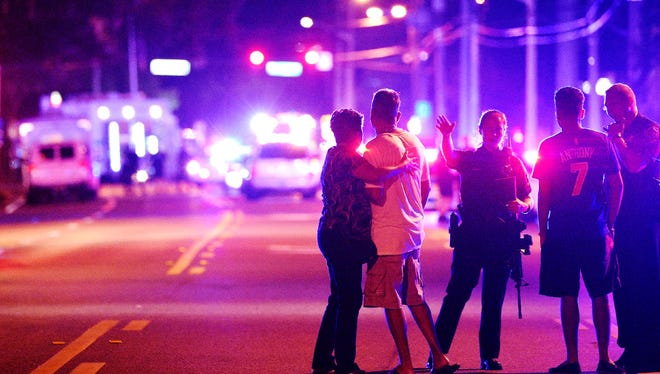Police officers direct family members away from a fatal shooting at Pulse nightclub in Orlando, Florida on June 12.