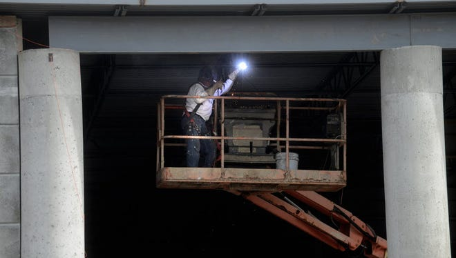 A welder works under a roof of a new building in Glen Rock earlier this year. Latest Challenger Gray & Christmas forecast is hopeful for job prospects for welders.