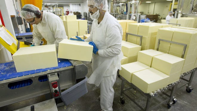 Employees load blocks of cheese that's about to be shredded at the company's headquarters plant in Plymouth.