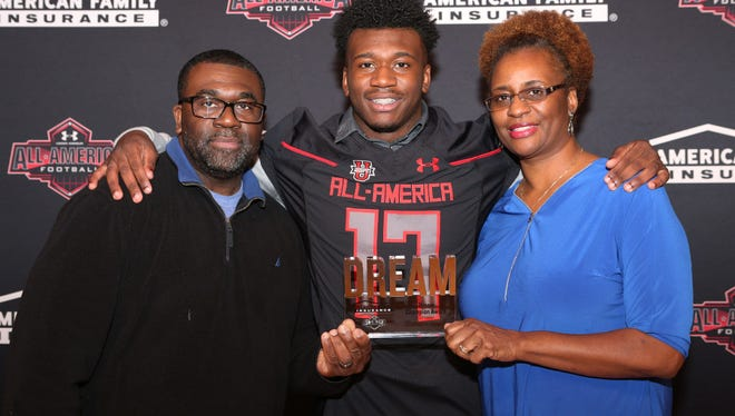 """From November: Paramus Catholic High School football LB Drew Singleton was a recipient of the American Family Insurance and Under Amour's """"All-American"""" team and received his jersey at a ceremony in the auditorium of the gym. Here, Drew poses with his jersey on and in the middle of his parents Duane and Bernadette Singleton holding the """"Dream Champion Award."""""""