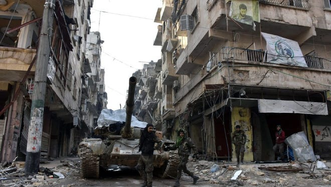 Syrian government soldiers walk near a tank in Zabadia and Salah Eddin district in Aleppo, Syria, on Dec. 23.