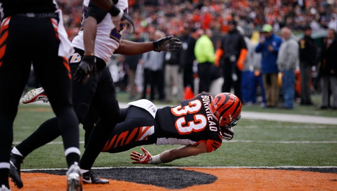 Bengals running back Rex Burkhead maintains his balance just enough to get over the goal line for Cincinnati's first score of the game Sunday against the Ravens at Paul Brown Stadium.