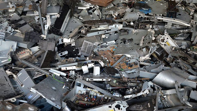 A pile of scrap computer components are piled at a breakage yard.