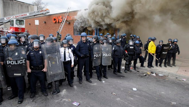 Police stand in front of a burning store, Monday, April 27, 2015, during unrest following the funeral of Freddie Gray in Baltimore.
