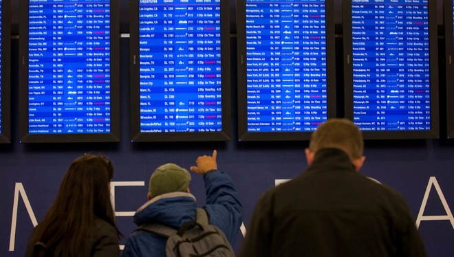 Travelers monitor the boards at Hartsfield-Jackson Atlanta International Airport on Jan. 6, 2017, in Atlanta.
