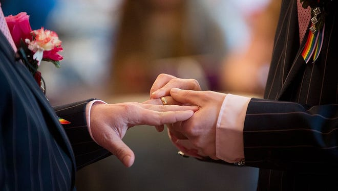 A file photo of two men exchanging rings during their wedding ceremony.