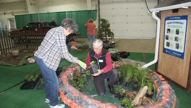Women set up a display for the garden show.