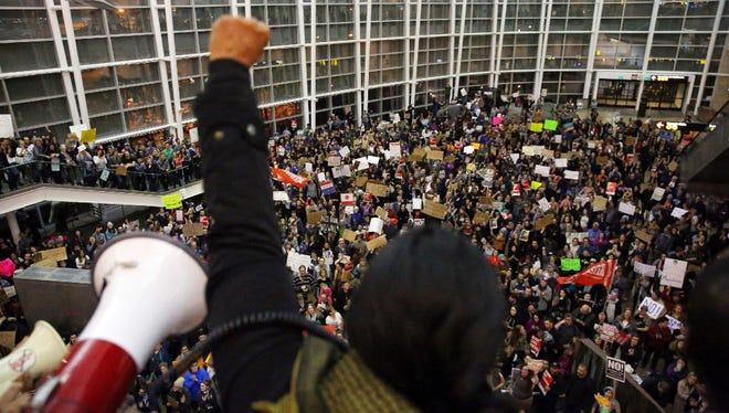Seattle city councilwoman and socialist activist Kshama Sawant raises a fist over the crowd, as more than 1,000 people gather at Seattle-Tacoma International Airport, to protest President Donald Trump's order that restricts immigration to the U.S., Saturday, Jan. 28, 2017, in Seattle. President Trump signed an executive order Friday that bans legal U.S. residents and visa-holders from seven Muslim-majority nations from entering the U.S. for 90 days and puts an indefinite hold on a program resettling Syrian refugees.