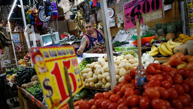 Vendor Luis Alberto Bautista arranges strawberries as he lays out fresh produce at the start of the day, in his vegetable stand in Mercado Medellin, in Mexico City, Thursday, Feb. 2, 2017. Mexico is the world's leading exporter of refrigerators and flat-screen TVs. Cars and trucks such as the Ram 1500 crew cab, Ford Fiesta and Chevrolet Trax fill U.S. dealer lots. Mexican berries, vegetables and beef born south of the border abound at American supermarkets.