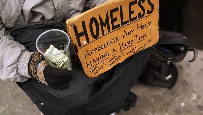 Person holding a sign saying they are homeless.