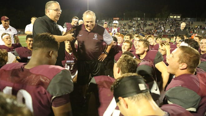 Former Don Bosco Prep football coach Greg Toal gets a prayer from school Director/President Jim Heuser after winning his 300th game last fall.