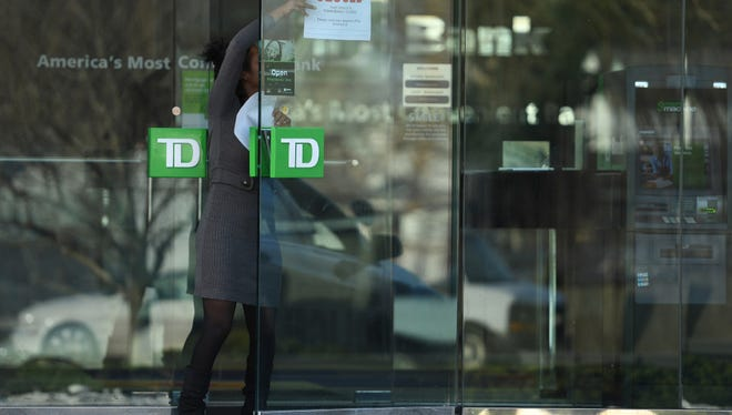 A closed sign is removed from a door at TD Bank on Boulevard in Hasbrouck Heights after a reported bank robbery on Saturday, Feb. 18, 2017.