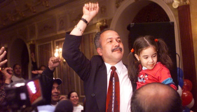 Joey Torres, with his daughter Joely, 3, at the Brownstone House in Paterson in 2002, reacting  to the news that he had defeated Mayor Martin G. Barnes.