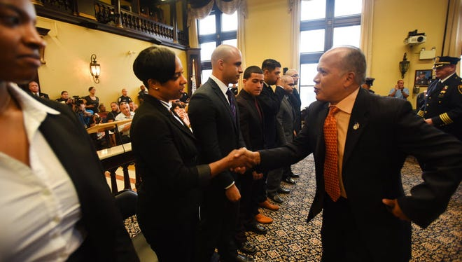Mayor Joey Torres shaking hands with new Paterson police officers after they were sworn in last year at City Hall.