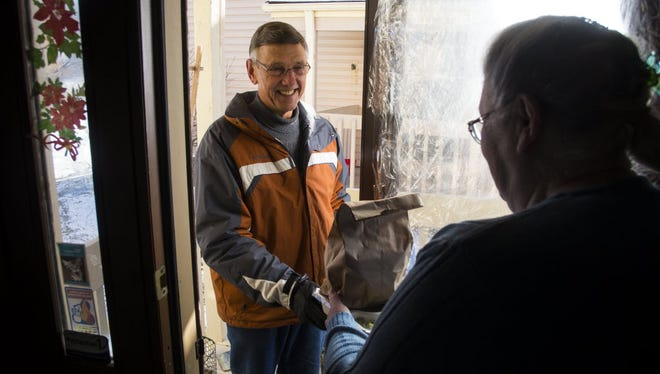 Jack Zimmer delivers a meal to Martha Scott in 2014 as  a volunteer for the Community Emergency Assistance Program (CEAP) in Brooklyn Center, Minn.