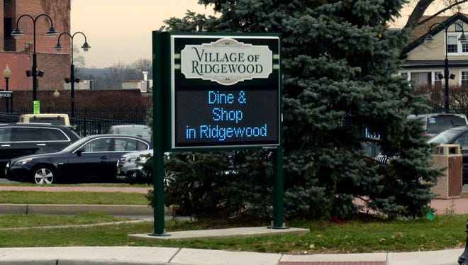 A sign in front of the Ridgewood train station.