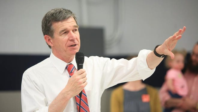 "N.C. Gov. Roy Cooper addresses the crowd during the United Way's ""Homework Diner"" April 25 at Enka Middle School. North Carolina Democrats and allies continued to press Republican leaders Monday to redraw legislative maps quickly after the U.S. Supreme Court affirmed last week that nearly 30 districts are illegally racially gerrymandered."