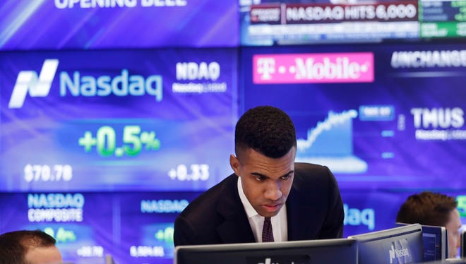 Brad Smith monitors stock prices at the Nasdaq MarketSite, Tuesday, April 25, 2017, in New York. The Nasdaq Composite rose above 6,000 Tuesday, a record high.