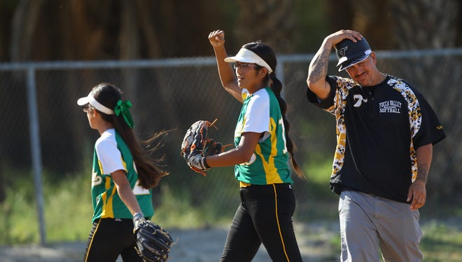 Coachella Valley High School softball team celebrates their win against Yucca Valley High School in Thermal on May 10, 2017 as Yucca Valley's coach laments on the right.