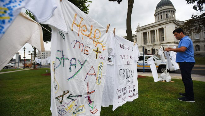 Anthony Torres, Clothesline Project facilitator from healingSpace, hangs up T-shirts with messages painted by survivors of domestic violence and sexual abuse, during the National Night Out event at Courthouse Green in Hackensack in August 2016.